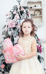 Girl stand near a Christmas fir-tree with toy heart in hands