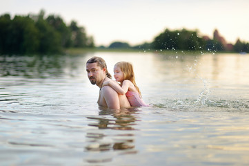 Little girl and her father having fun in a river