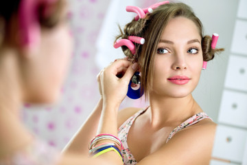 Young  girl front  the mirror puts earring