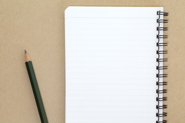 blank notebook and pencil on wooden table