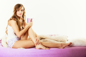 Girl relaxing on bed at morning with tea cup