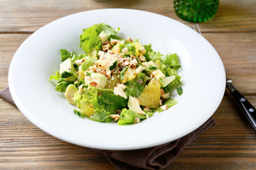 Fresh salad with avocado, orange and crushed nuts on a bowl