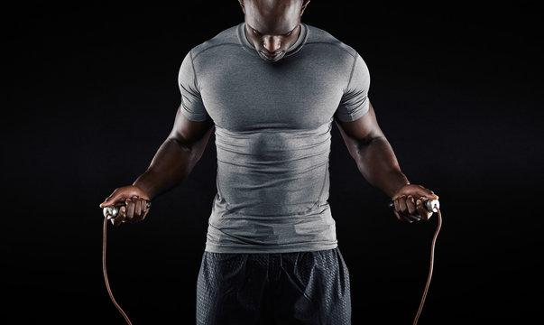 Muscular man skipping rope