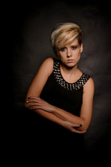 Beautiful blonde with short hair on a dark background