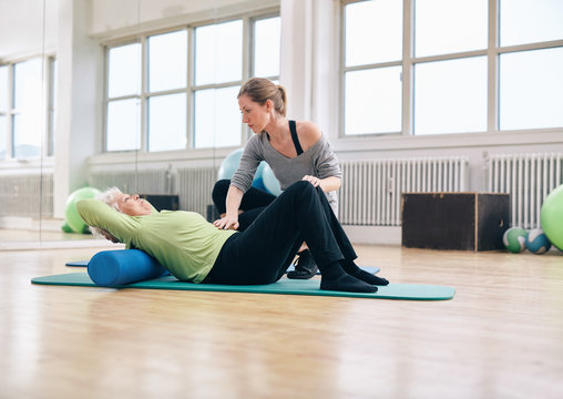 Physical therapist helping elder woman at gym