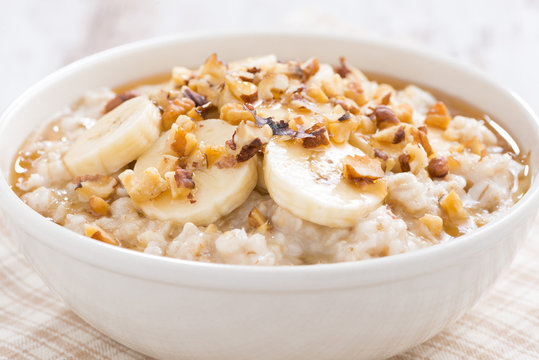 oatmeal with banana, honey and walnuts in bowl, close-up