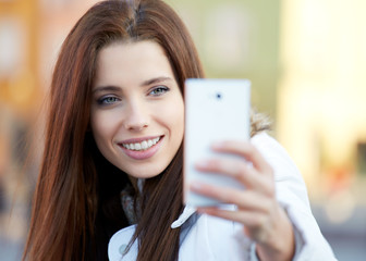 pretty young woman taking a picture on town. Smiling girl. Winte
