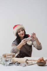Happy young housewife making christmas cookies in kitchen