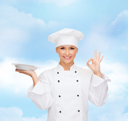 female chef with empty plate showing ok sign