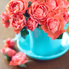 Beautiful tea roses in a blue cup on a table.