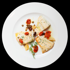 Fried fish fillet with capers isolated on black