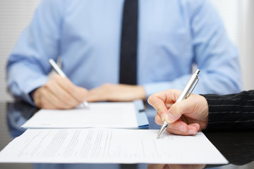 Man and woman   signing a business contract after the conclusion