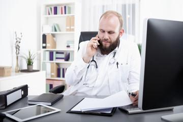 Arzt telefoniert und schaut in den Computer Bildschirm
