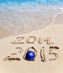 On sand it is written 2014 and 2015 and the New Year's ball lies