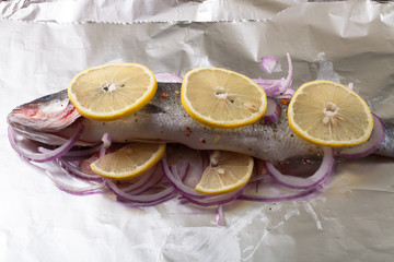 Fish prepared for roasting on the foil with lemon and onion.