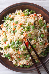 Asian fried rice with egg and vegetables top view vertical
