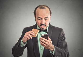 surprised business man eating on a go cookie using smartphone