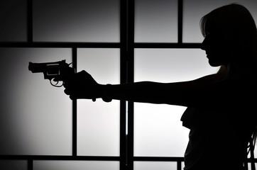 Silhouette of fashion killer woman with revolver gun