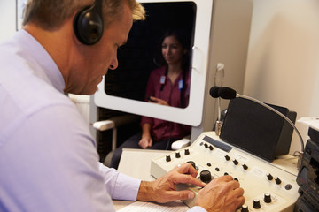 Audiologist Carrying Out Hearing Test On Female Patient