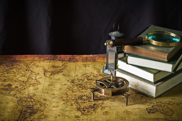 Magnifier with lantern with compass on the old map