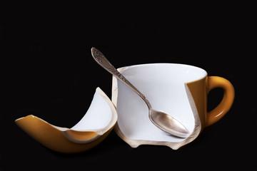 Broken coffee cup, black background