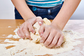 Kneading dough on girl hands