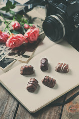 Vintage camera, old photos and roses, toned image