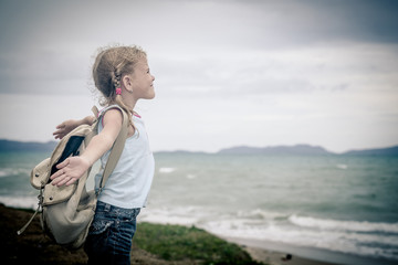 Little girl with a backpack standing on the beach