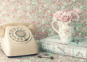 Bouquet of roses in a coffee cup and vintage telephone