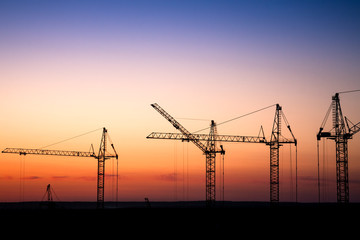 construction site with cranes against a sunset sky