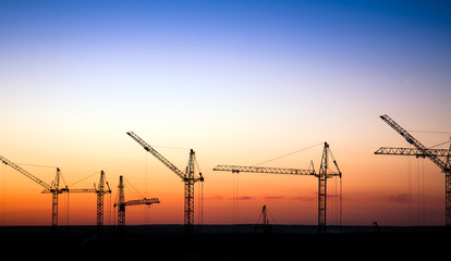 Cranes on a construction site against a sunset sky
