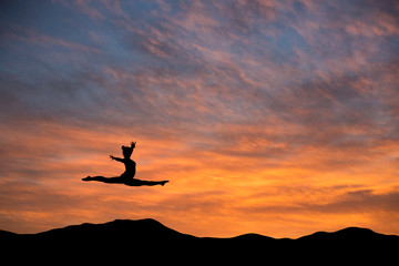Wall Mural - silhouetted gymnast doing the splits jump in sunset