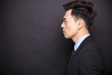 side view businessman standing before black background