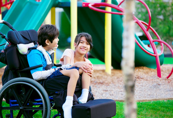 Sister sitting next to disabled brother in wheelchair at playgro