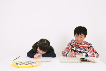 색칠 공부하는 여자아이와 공부하는 남자아이