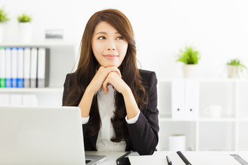 smiling young business woman thinking in the office