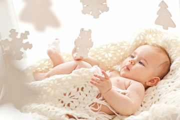 Cute little girl play with wood snowflakes in her cozy white bed