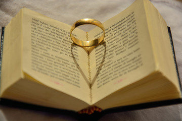 heart shaped shadow of a ring reflecting on a book