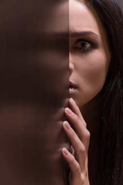 Beautiful young brunette woman looking scared.