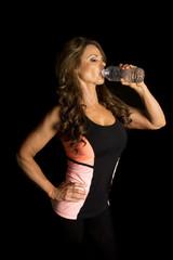 woman on black drinking water fitness attire