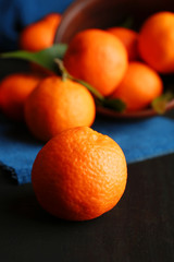 Fresh ripe mandarins on napkin, on dark wooden background