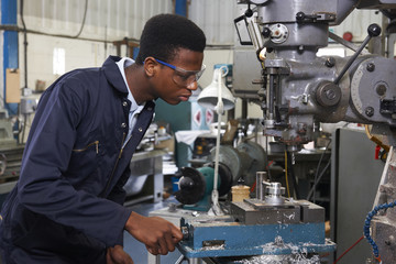 Male Apprentice Engineer Working On Drill In Factory