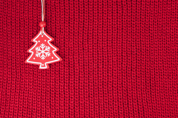 Christmas fir tree decoration on red wool knitted fabric