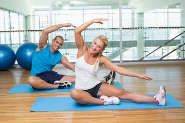 Portrait of couple stretching hands in yoga class