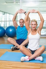 Couple stretching up hands in yoga class