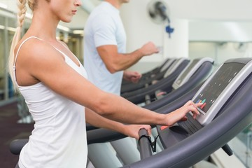 Side view mid section of couple running on treadmills at gym