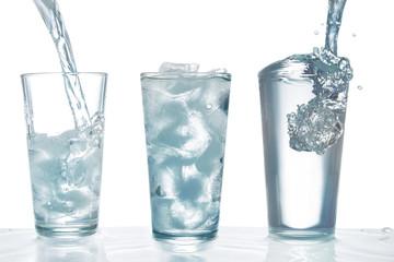 Trinkwasser aus einer Flasche in ein Glas mit Eiswürfeln gießen