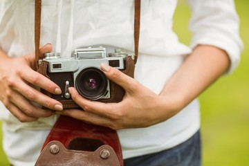Mid section of woman holding vintage camera
