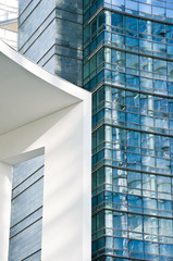 Glass Facade of company building with reflection of blue sky.