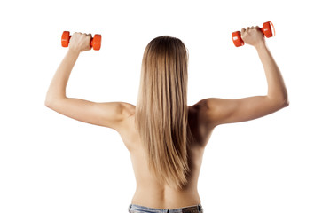rear view on a pretty muscular blonde with weights in her hands